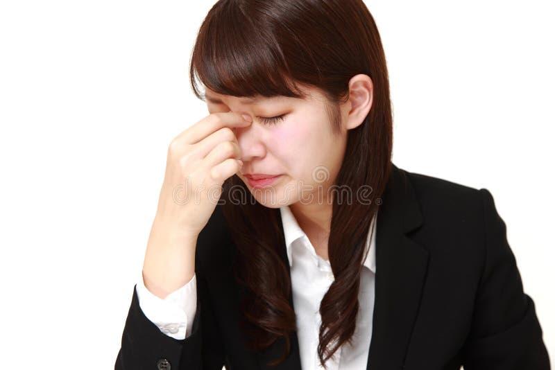 La giovane donna di affari giapponese soffre da astenopia fotografia stock libera da diritti
