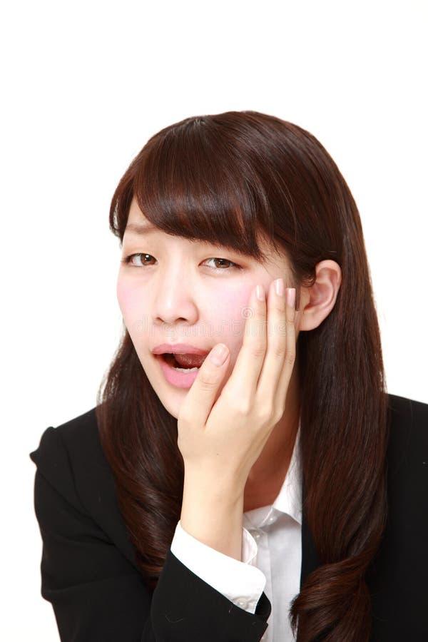 La giovane donna di affari giapponese soffre da mal di denti fotografia stock libera da diritti