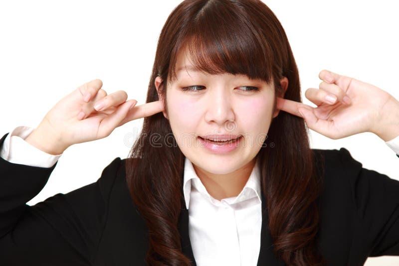 La giovane donna di affari giapponese soffre da rumore immagine stock libera da diritti
