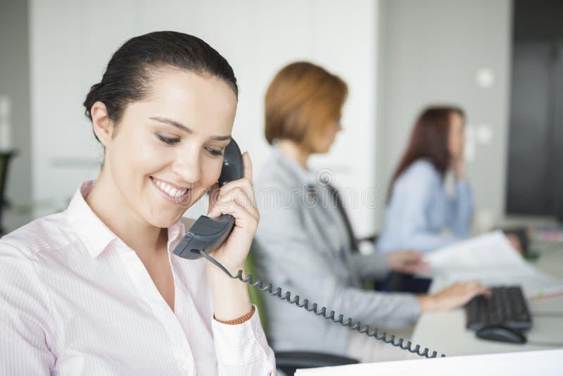La giovane donna di affari sorridente che usando la linea terrestre telefona con i colleghi nel fondo all'ufficio fotografia stock libera da diritti