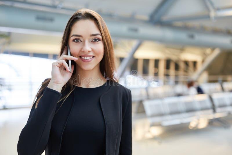 La giovane donna di affari sta telefonando con il telefono cellulare nell'aeroporto fotografia stock
