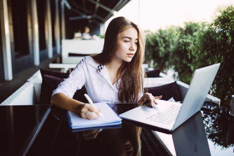 La giovane donna di affari in vestito giallo che si siede alla tavola in caffè e che scrive in taccuino sulla tavola è computer p fotografia stock libera da diritti