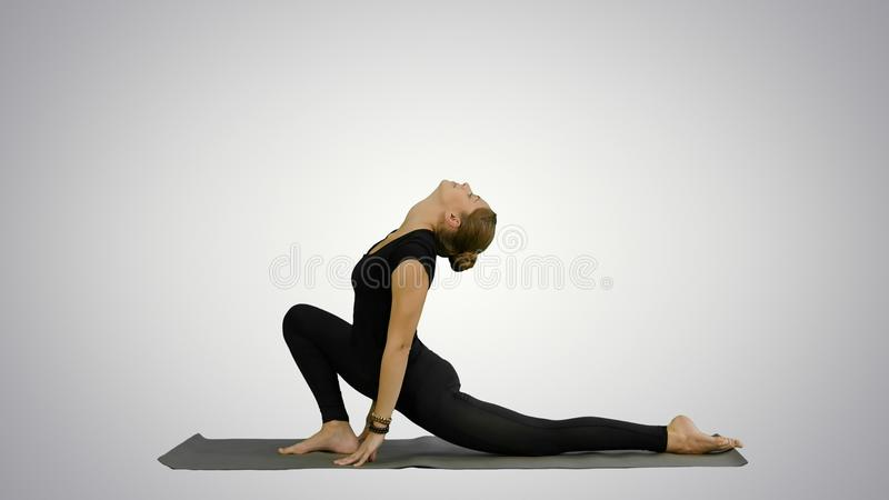 La giovane donna di Bbeautiful che porta gli abiti sportivi neri che risolvono, facendo l'yoga o i pilates si esercita su fondo b immagini stock