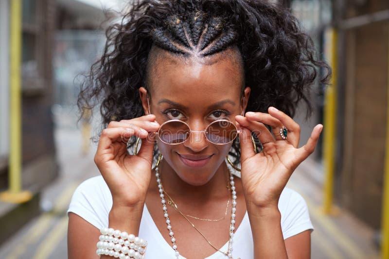 La giovane donna di colore con gli occhiali da sole guarda alla macchina fotografica, ritratto fotografia stock