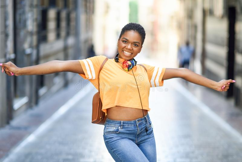 La giovane donna di colore sta ballando sulla via di estate Ragazza che viaggia da solo fotografia stock