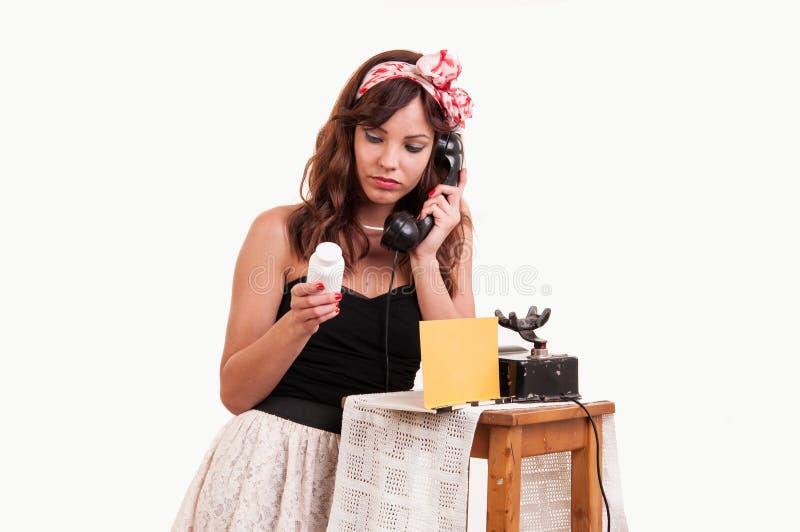 La giovane donna di modo con un retro sguardo parla ad un telefono d'annata fotografia stock libera da diritti