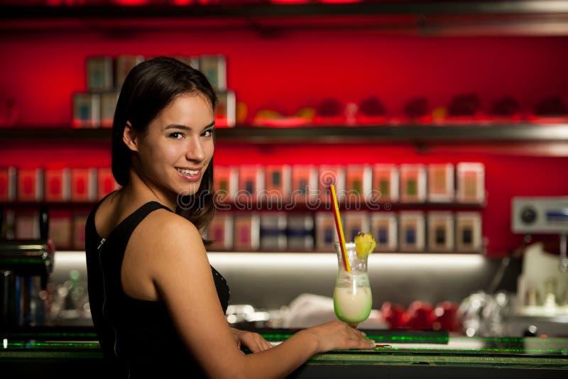 La giovane donna di Preety beve il cocktail in un night-club immagini stock
