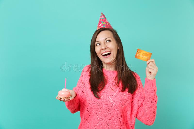 La giovane donna di risata in cappello rosa tricottato di compleanno del maglione che cerca il dolce disponibile della tenuta con fotografia stock