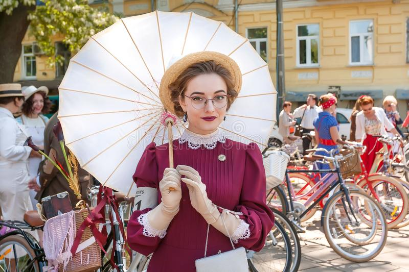 La giovane donna di vecchio modo si veste con l'ombrello che raffredda alla retro crociera di festival fotografia stock
