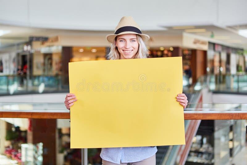 La giovane donna di vendita sta tenendo l'insegna in bianco gialla fotografia stock libera da diritti