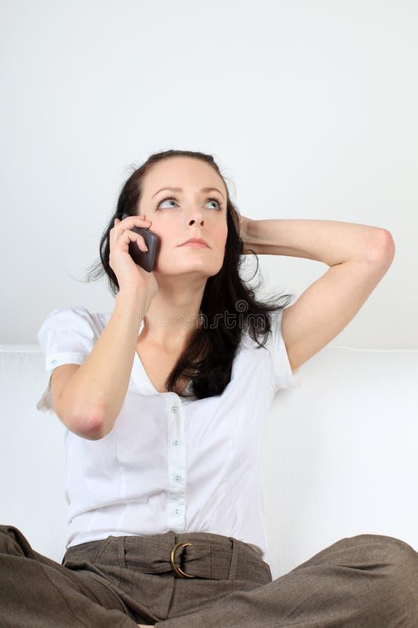 La giovane donna disperata comunica tramite suo telefono cellulare che ha sua mano in capelli fotografia stock libera da diritti