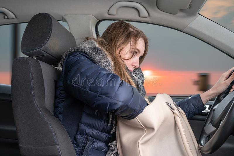La giovane donna ? distratta mentre conduce l'automobile fotografia stock