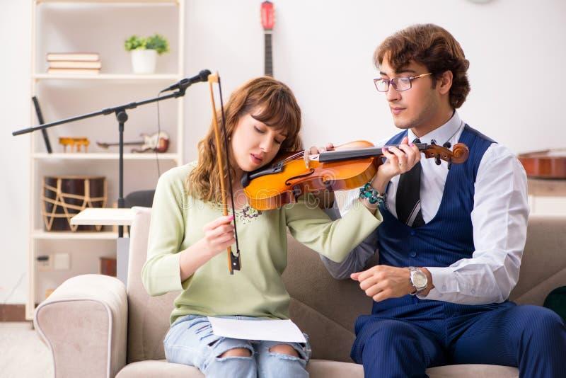 La giovane donna durante la lezione di musica con l'insegnante maschio fotografia stock