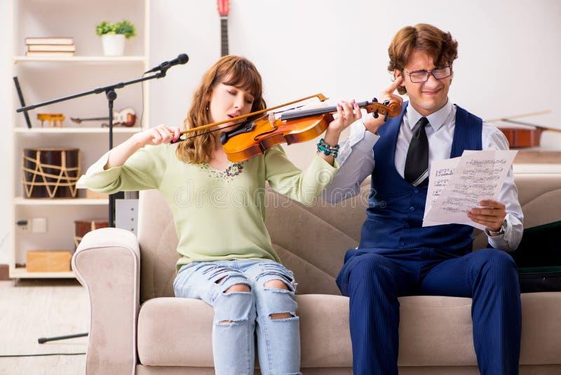 La giovane donna durante la lezione di musica con l'insegnante maschio immagine stock libera da diritti