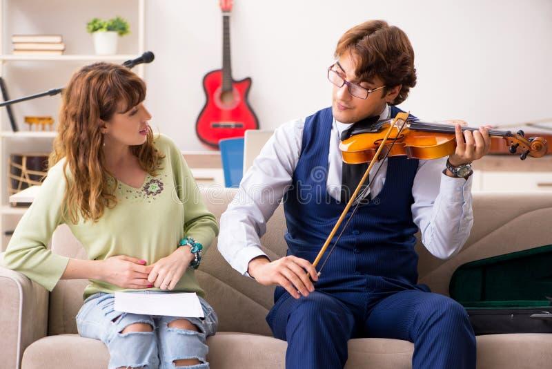 La giovane donna durante la lezione di musica con l'insegnante maschio fotografie stock libere da diritti
