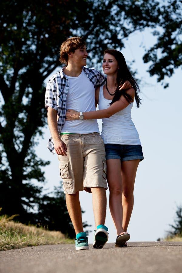 La giovane donna e l'uomo sta camminando su una strada di estate all'aperto immagini stock