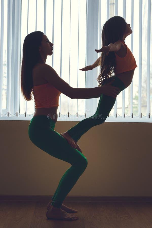 La giovane donna e la bambina che praticano l'yoga dura posano, siluetta vicino alla finestra, piena crescita fotografia stock libera da diritti