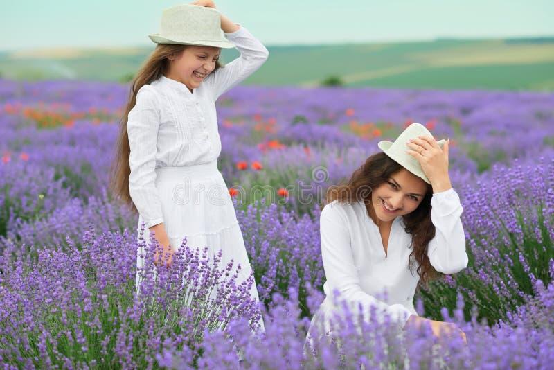 La giovane donna e la ragazza sono nel giacimento della lavanda, bello paesaggio dell'estate con i fiori rossi del papavero fotografia stock
