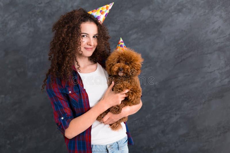 La giovane donna ed il suo cane celebrano il compleanno fotografia stock