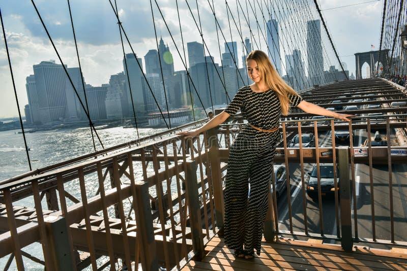 La giovane donna elegante si è vestita in tuta alla moda che sta sul ponte di Brooklyn fotografia stock