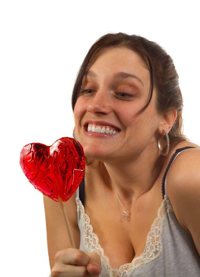 La giovane donna esamina il lollipop a forma di cuore immagine stock libera da diritti