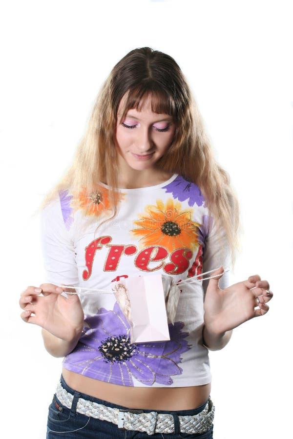 La giovane donna esamina un regalo immagini stock