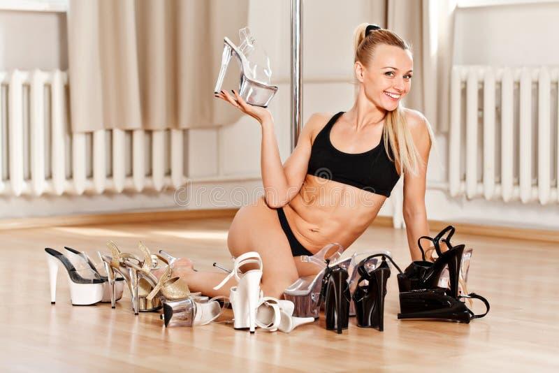 La giovane donna esile di ballo del palo che sceglie le scarpe per la striscia prende in giro fotografia stock libera da diritti