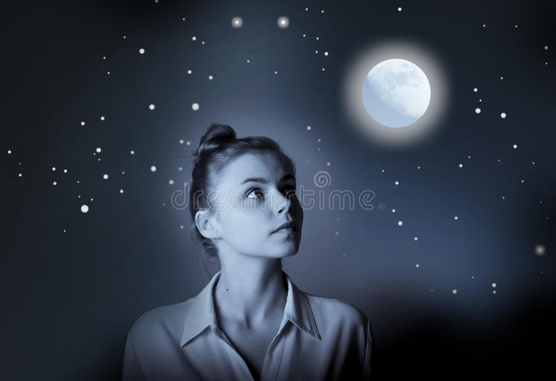 La giovane donna esile sta guardando in pieno la luna immagini stock libere da diritti