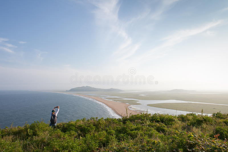 La giovane donna esile sta su un'alta collina ed ha fotografato una vista magnifica del mare e della costa immagine stock libera da diritti