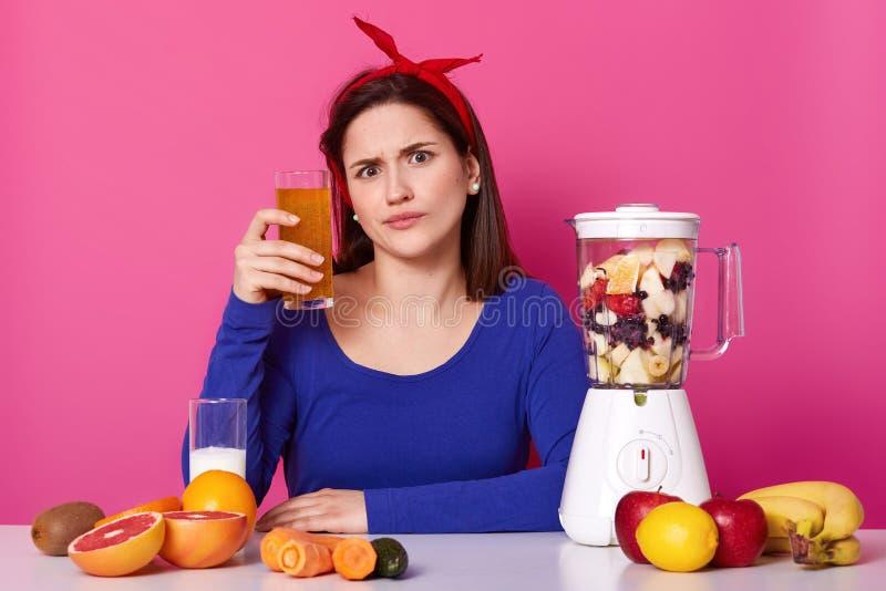 La giovane donna europea emozionale si siede alla tavola con l'attrezzatura della cucina, varia frutta su, tenendo il vetro del f fotografia stock