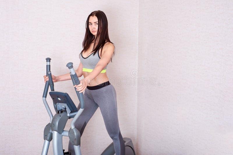 La giovane donna fa gli esercizi a casa sull'elissoide Il concetto di uno stile di vita sano fotografia stock libera da diritti