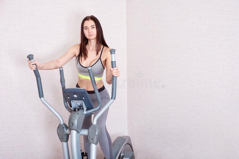La giovane donna fa gli esercizi a casa sull'elissoide Il concetto di uno stile di vita sano immagini stock