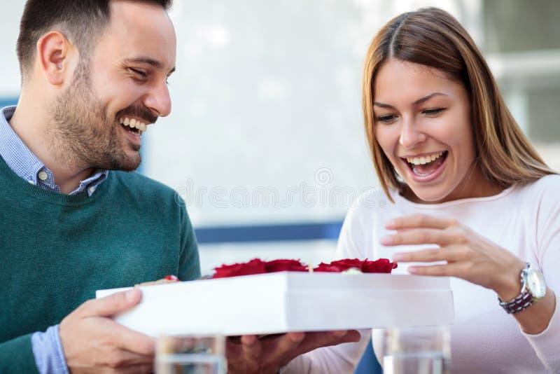 La giovane donna felice è sorpresa dopo la ricezione del contenitore di regalo con le rose ed i dolci dal suo ragazzo o marito fotografia stock