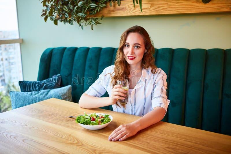 La giovane donna felice beve l'acqua nel bello interno con i fiori verdi sui precedenti e gli ingredienti freschi sulla tavola fotografie stock