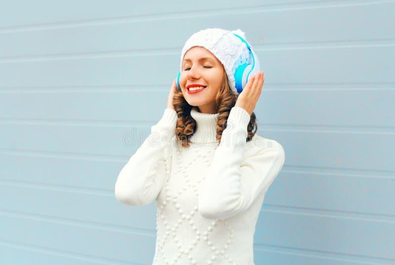 La giovane donna felice in cuffie gode di ascolta musica che porta un cappello tricottato, maglione sopra il blu immagini stock libere da diritti