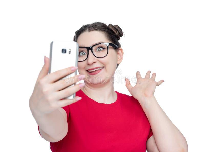 La giovane donna felice divertente in vetri con lo smartphone fa il selfie, su fondo bianco fotografia stock