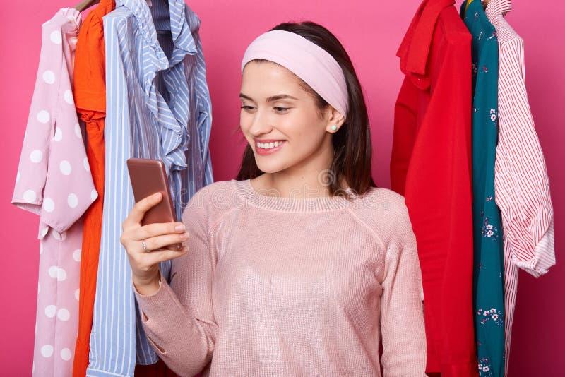 La giovane donna felice esamina l'esposizione del telefono cellulare Ganci dei vestiti alla moda La ragazza di Smilling rinfresca fotografia stock