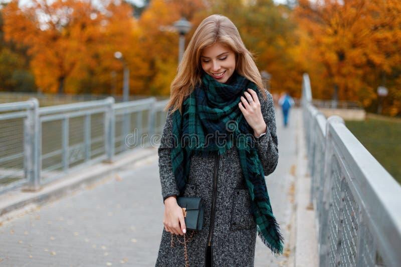 La giovane donna felice graziosa in un cappotto alla moda di autunno d'annata in una sciarpa verde alla moda con una borsa di cuo immagine stock libera da diritti