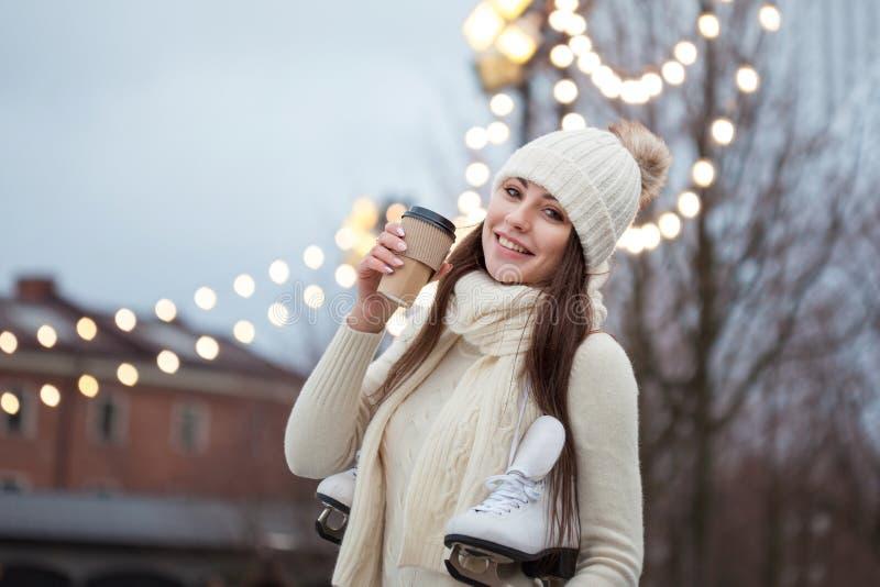 La giovane donna felice in maglione e cappello tricottati è caffè andante delle bevande e pattinare fotografie stock