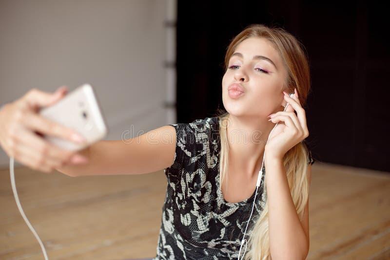 La giovane donna felice prende un selfie mentre musica d'ascolto che si siede sul pavimento con le cuffie fotografie stock libere da diritti