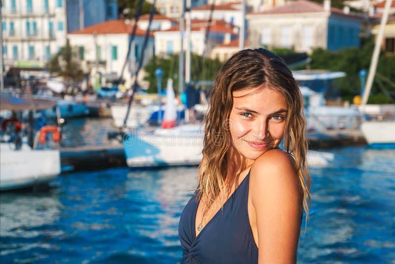 La giovane donna felice ritiene il divertimento sul catamarano di lusso dell'yacht della barca a vela nel mare del turchese nelle immagini stock