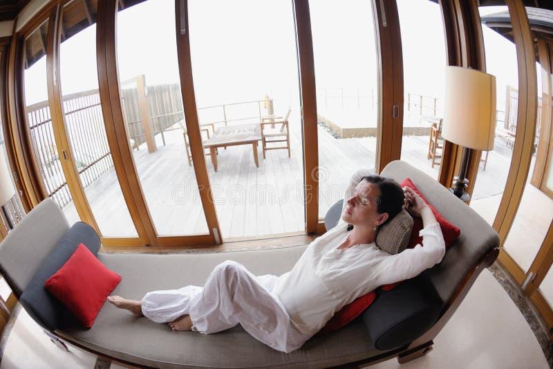 La giovane donna felice si rilassa a casa sul sofà immagini stock