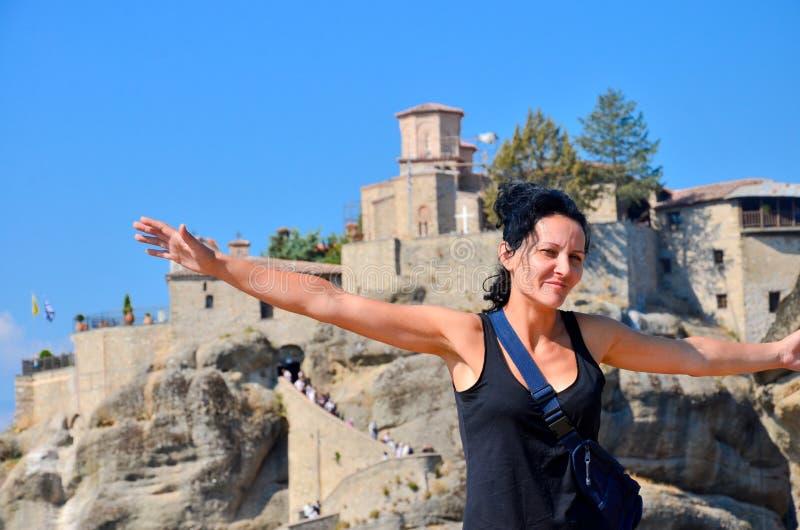 La giovane donna felice sta di nuovo alla roccia con le mani sollevate ed al monastero a fondo fotografia stock