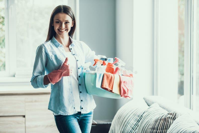 La giovane donna felice tiene le attrezzature per la pulizia a casa fotografie stock libere da diritti