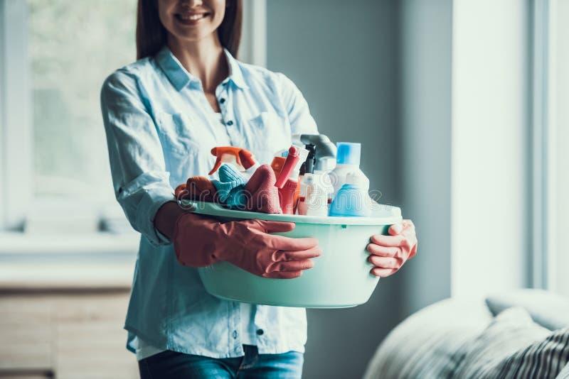 La giovane donna felice tiene le attrezzature per la pulizia a casa immagine stock libera da diritti