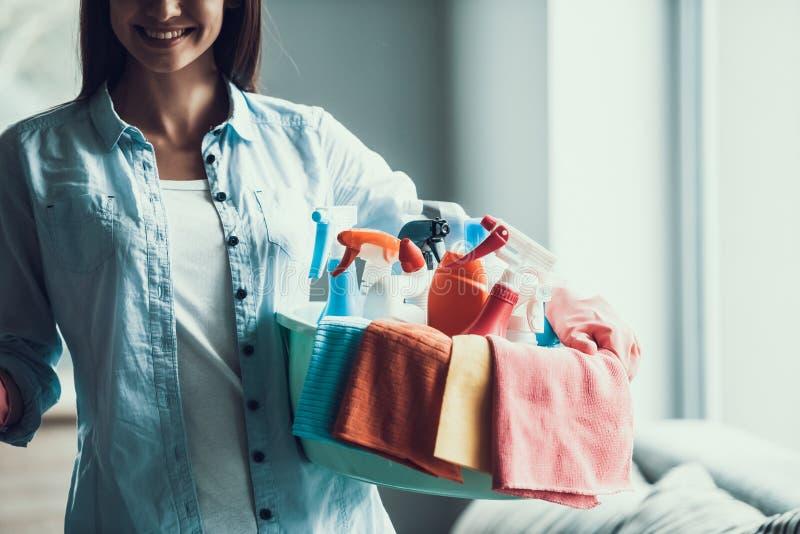 La giovane donna felice tiene le attrezzature per la pulizia a casa fotografia stock