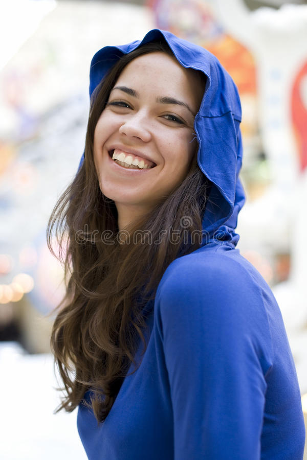 La giovane donna felice in un cappuccio blu scuro sorride immagini stock