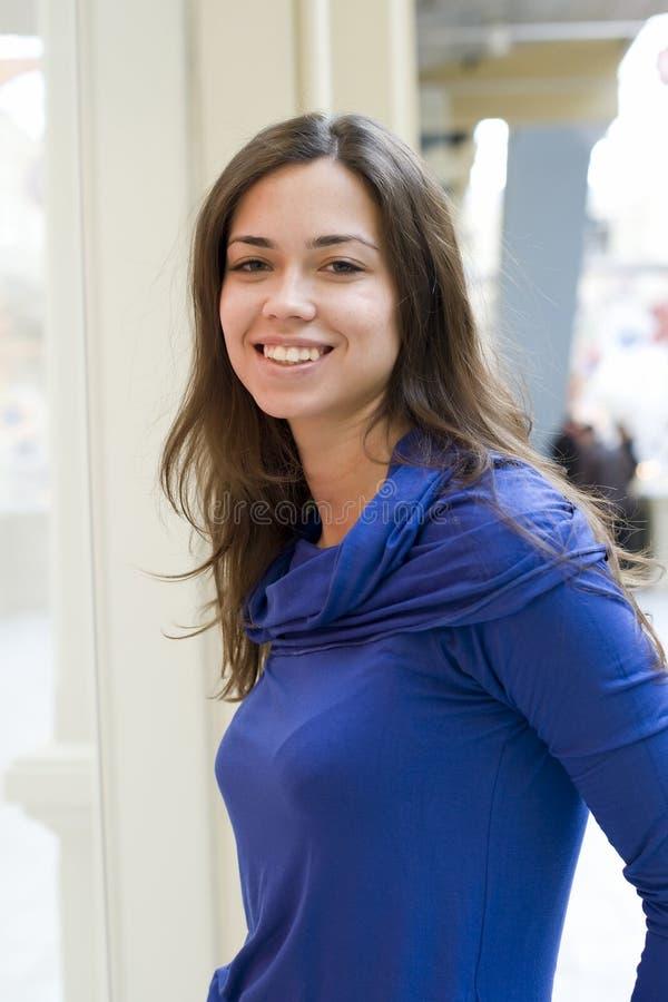 La giovane donna felice in un rivestimento blu scuro immagine stock libera da diritti