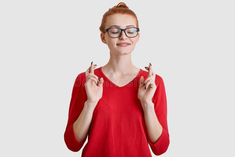La giovane donna Freckled dello zenzero tiene le dita attraversate, crede nella fortuna, indossa gli occhiali quadrati ottici, in fotografia stock libera da diritti