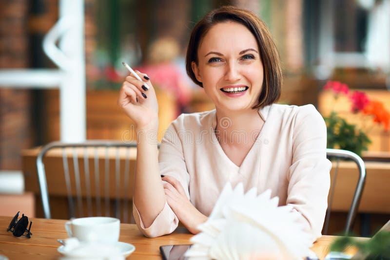 La giovane donna fuma il tabacco in un caffè fotografia stock libera da diritti
